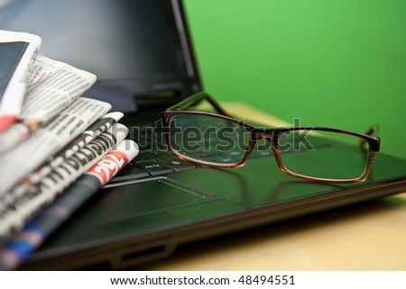 Newspapers laptop glasses in composition on green background - stock photo