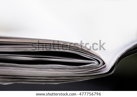 Newspapers on black table and white background, with shallow depth of field