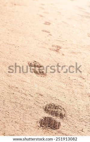 Next from the sole of a shoe in the sand.Steps in the sand. - stock photo