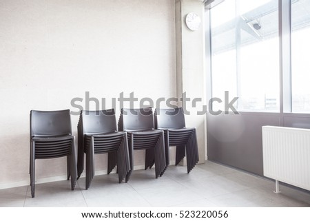 next to the window in the room, there are stacked chairs