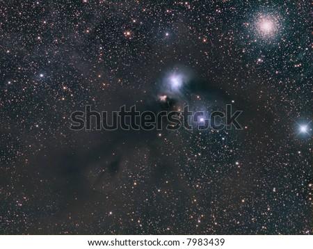 NGC 6723 dusty nebula and NGC 6727 globular cluster in Corona Australis - stock photo
