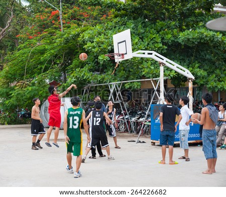 NHA TRANG, VIETNAM - AUG 5, 2014: Unidentified teenagers play basketball in a yard in the downtown. The city is a very popular fast developing sea resort. - stock photo