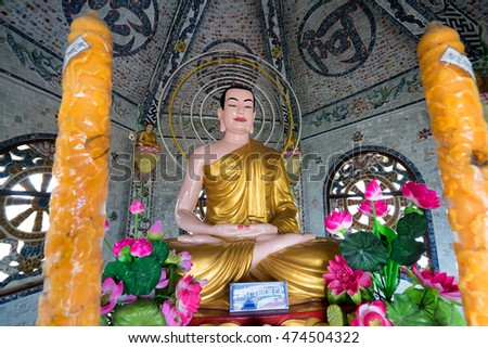 NHA TRANG, VIETNAM - JUNE 23, 2016: Big statue of Buddha in a gold cape inside the temple. Nearby there are two big candles and beautiful flowers