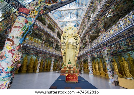 NHA TRANG, VIETNAM - JUNE 23, 2016: Internal furniture of the Buddhist temple. Gold statue of Buddha in the middle of the hall. Walls are painted with multi-colored drawings.