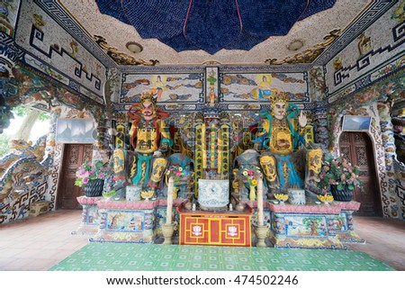 NHA TRANG, VIETNAM - JUNE 23, 2016: Statues of gods in the Buddhist temple. Walls and floor are made of a multi-colored mosaic