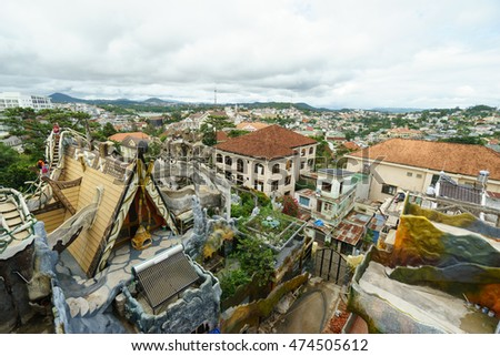 NHA TRANG, VIETNAM - JUNE 23, 2016: View to roofs of fairy tale's buildings in an amusement park and local houses on the background in Vietnam