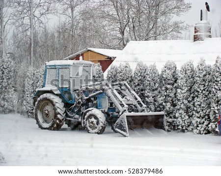 NICA, LATVIA - DECEMBER 3, 2016: After snowfall tractor in farm yard is covered with snow.