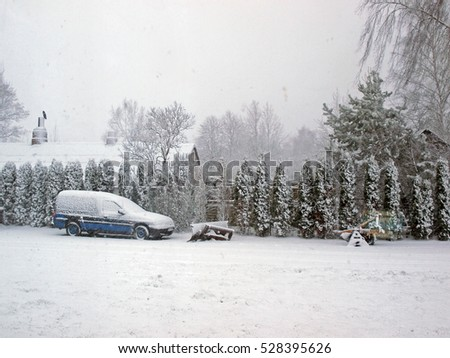 NICA, LATVIA - DECEMBER 3, 2016: Snowfall is covering country farm yard and car with snow.