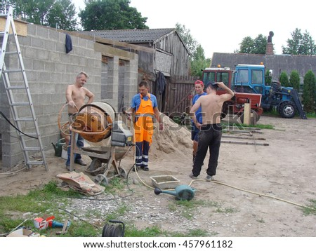 NICA, LATVIA - JULY 24, 2016: Construction workers are making grout with electric mixer from grawel and cement.                                - stock photo