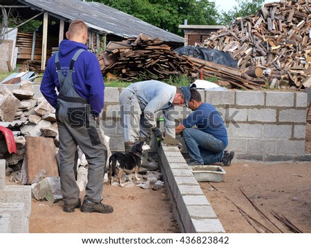 NICA, LATVIA - JUNE 13, 2016: Construction workers masons are building the wall from ceramsite blocks. - stock photo