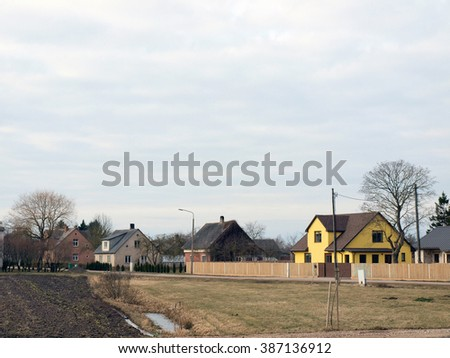 NICA, LATVIA - MARCH 2, 2016: Outskirts bystreet has small private houses and gardens along it. - stock photo