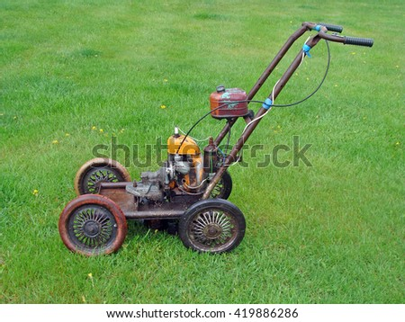 NICA, LATVIA - MAY 13, 2016: Homemade lawn mower is made from russian chain saw engine and baby carriages wheels.