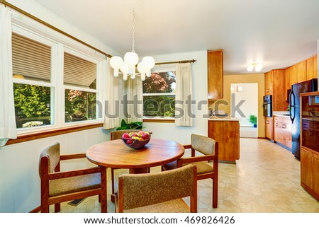 Nice American dining room with round dinner table and fruit basket on it. The room is connected with the kitchen area. Northwest, USA