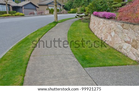Nice and clean sidewalk and the empty street. Neighborhood scenery, landscape design.
