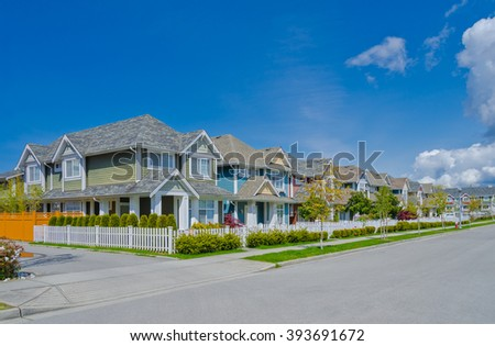 Nice and comfortable great neighborhood. Some homes behind white wooden fence on the empty street in the suburbs of Vancouver, Canada. - stock photo