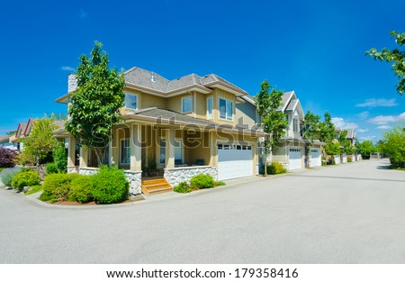 Nice and comfortable neighborhood. A House on the corner of empty street and a row, line of the houses with garages, homes in the suburbs of the North America. Canada. - stock photo