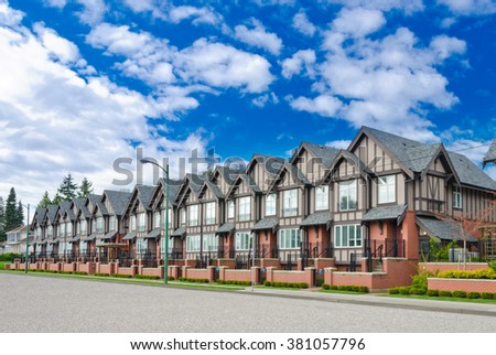 Nice and comfortable neighborhood. A row, line of the townhouses, homes on empty street in the suburbs of Vancouver, Canada. - stock photo