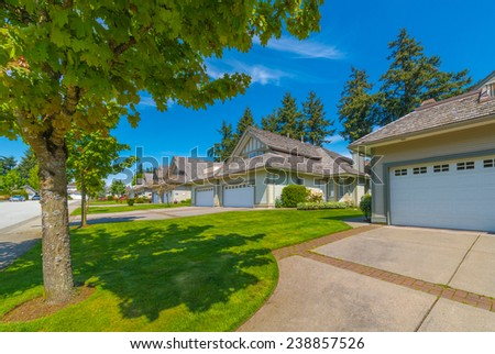 Nice and comfortable neighborhood. A row of homes with garages on the empty street in the suburbs of Vancouver, Canada. - stock photo
