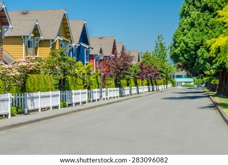 Nice and comfortable neighborhood, community. Some, line of homes behind the fence on empty street in the suburbs of the North America. Canada. - stock photo