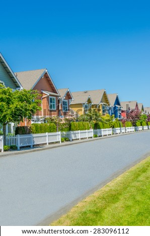 Nice and comfortable neighborhood, community. Some, line of homes behind the fence on empty street in the suburbs of the North America. Canada. Vertical. - stock photo