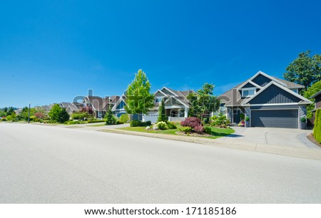 Nice and comfortable neighborhood. Long raw of the homes on empty street in the suburbs of the North America. Canada. - stock photo