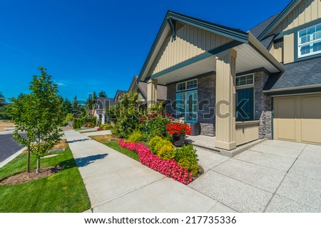 Nice and comfortable neighborhood. Some homes on the empty street and pedestrian sidewalk  in the suburbs of the North America. Canada. - stock photo