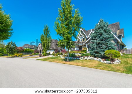 Nice and comfortable neighborhood. Some homes on the empty street in the suburbs of the North America, Vancouver, Canada. - stock photo