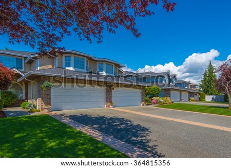 Nice and great neighborhood. Some homes with garages on the empty street in the suburb of North America. Canada. - stock photo