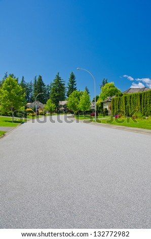 Nice and quiet neighborhood. Empty road in the suburbs of Vancouver, Canada. - stock photo