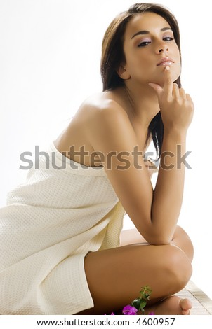 nice and young woman sitting on a wood carpet wearing a white towel - stock photo