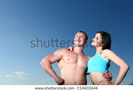 Nice athletic man and woman standing next to each other against the blue sky - stock photo