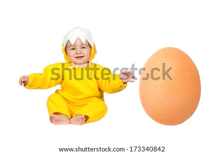 Nice baby chick disguised with a big egg at his side isolated on a white background - stock photo
