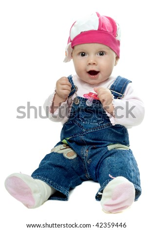 Nice baby girl in jeans suit playing with a dummy. Isolated