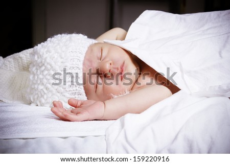 nice baby sleeps in a white knitted cap - stock photo