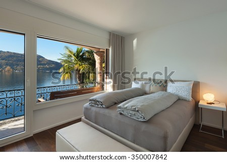 Nice bedroom with large window, view of the lake - stock photo