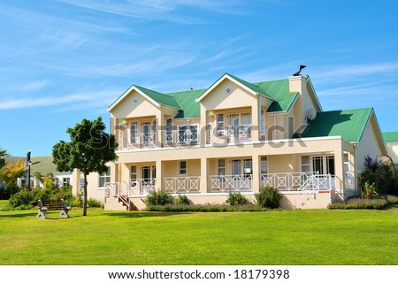 Nice big house, lawn, bench, tree. Shot in Kuils River Winelands, near Stellenbosch/Cape Town, Western Cape, South Africa. - stock photo