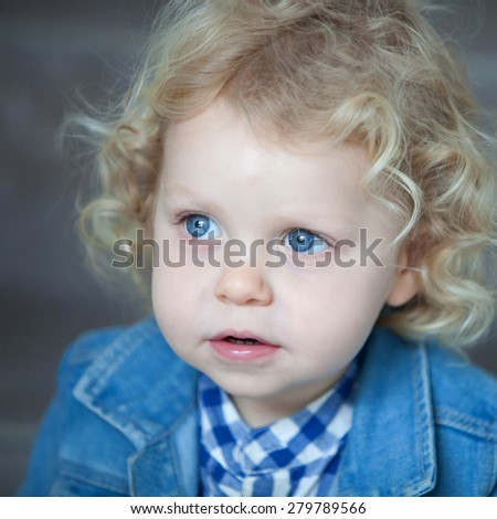 Nice blond baby with blue eyes and curly hair - stock photo