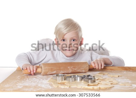 Nice blond smiling boy with angel wings at Christmas bakery from shortcrust cookies with dough, flour, metal cutter, wooden rolling pin and rolling board on the white background isolated horizontal - stock photo