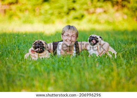 Nice blonde and cheerful young woman with her dogs resting on green lawn in the park. - stock photo