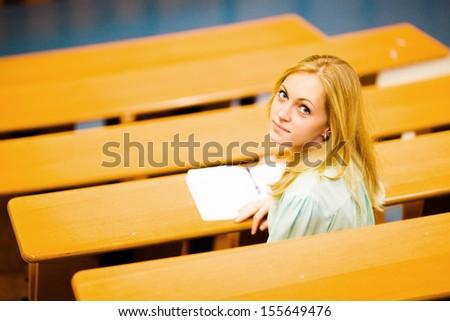 Nice blonde blue-eyed student girl in auditorium writing down turned around - stock photo