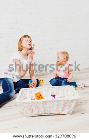 Nice blonde haired girl blowing bubbles to her little sister sitting on floor - stock photo