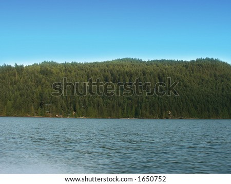 Nice blue sky above mountains and a lake - stock photo