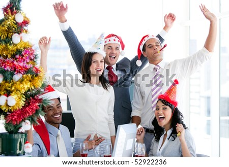 Nice business team punching the air to celebrate christmas in the office - stock photo
