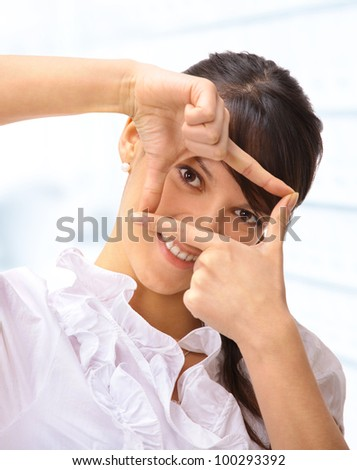 Nice business woman in the office, looking through the window of his fingers. - stock photo