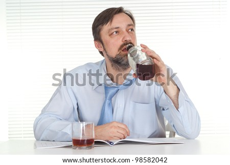 Nice businessman sitting at a table with a bottle on a light background - stock photo