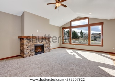 Nice carpet unfurnished living room with fireplace. - stock photo