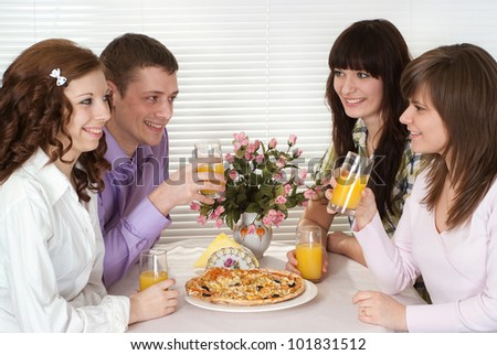 Nice Caucasian charming company of four people sit and eat pizza at a cafe - stock photo