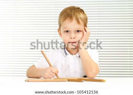 Nice Caucasian male sitting at the table draws on a light background - stock photo