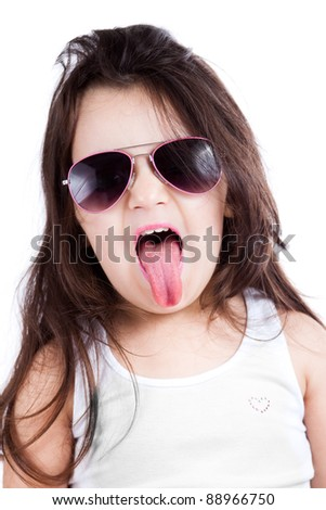 Nice child girl wearing a grey shirt isolated on white, showing her tongue in a cool and funny way, wearing sunglasses. - stock photo