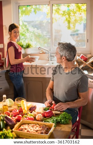 Nice couple cooking together a vegetable meal in the kitchen by a sunny day. The grey haired man is cutting a tomato and the woman is doing the dishes. They are wearing casual clothes.